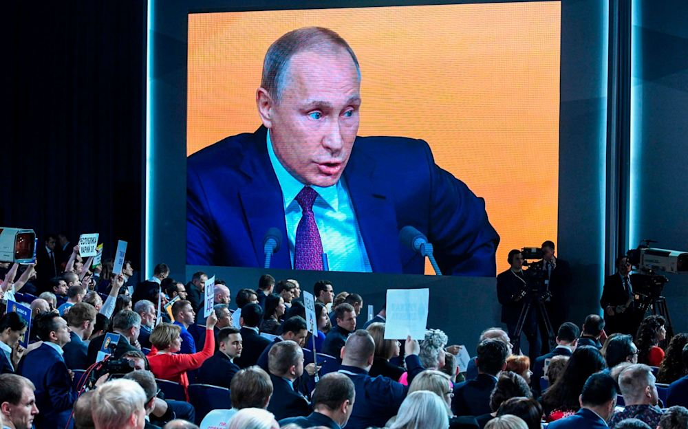 A video screen displays Russian President Vladimir Putin speaking during his annual press conference in Moscow while journalists hold placards - AFP