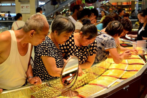 Customers look at gold necklaces at a jewelry store in Xuchang