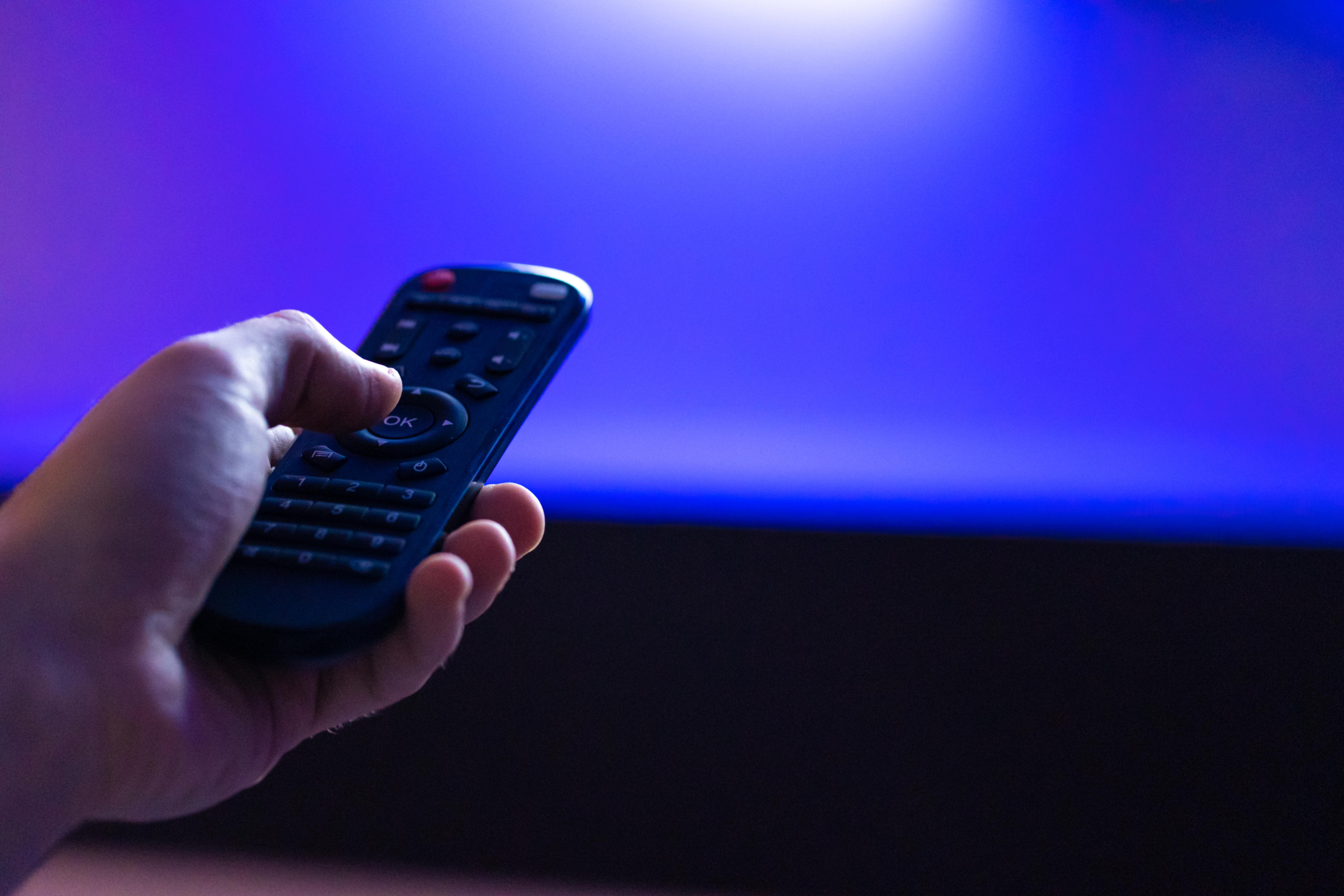 leisure at home. Watch TV. Remote control in hand close-up.