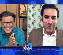 Rudy Giuliani had an ex-cop guarding the door in that Borat hotel scene, Sacha Baron Cohen tells Colbert