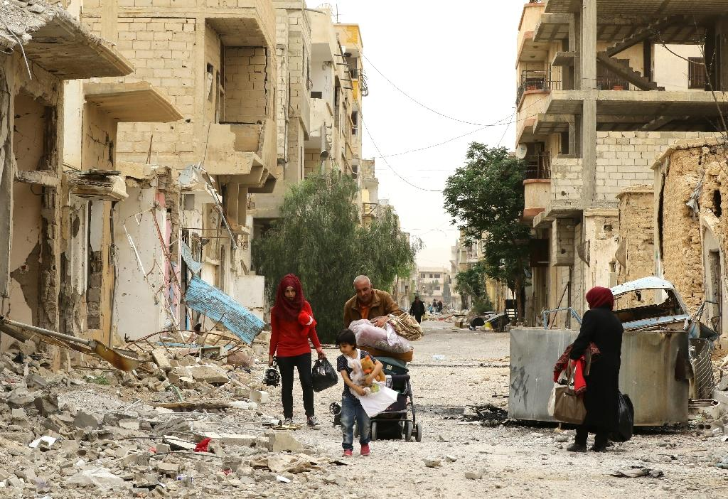 Syrians clamber over debris as they return to the modern town of Palmyra on April 9, 2016