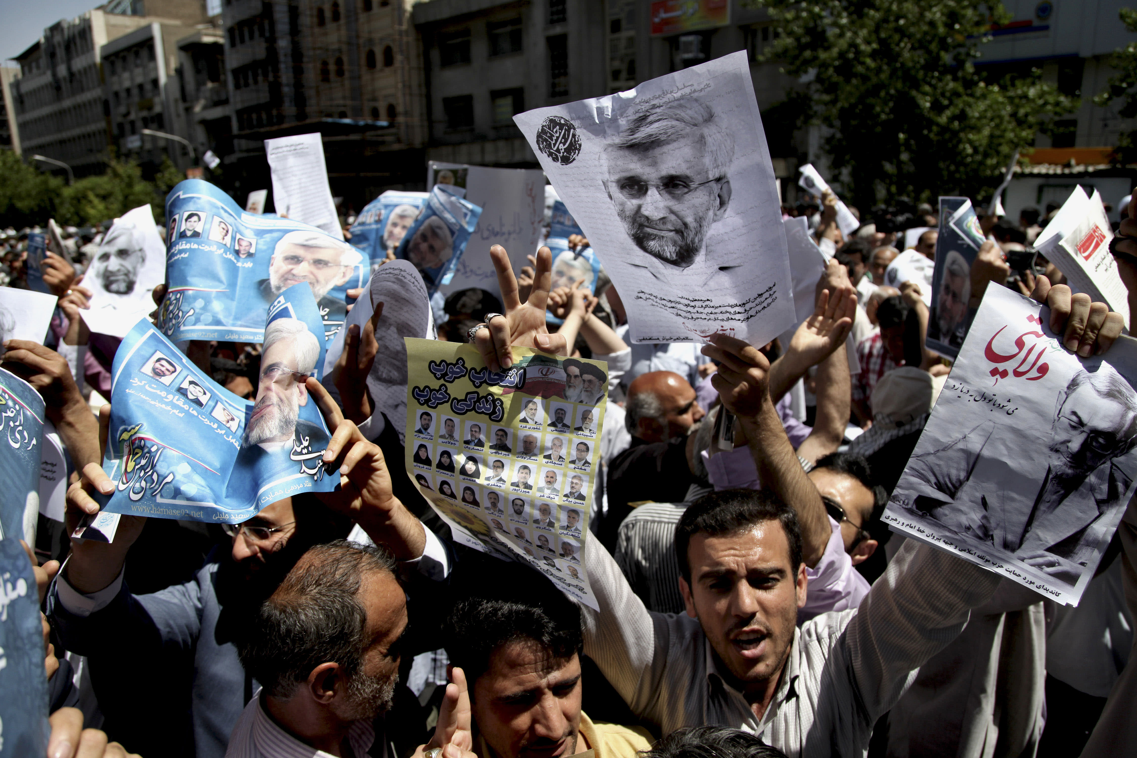Supporters of the presidential candidates, Ali Akbar Velayati, shown in the poster at right, and Saeed Jalili, center on the poster, attend a street campaign after Friday prayers in Tehran, Iran, Friday, June 7, 2013. Iranian Presidential election will be held on June 14, 2013. (AP Photo/Ebrahim Noroozi)