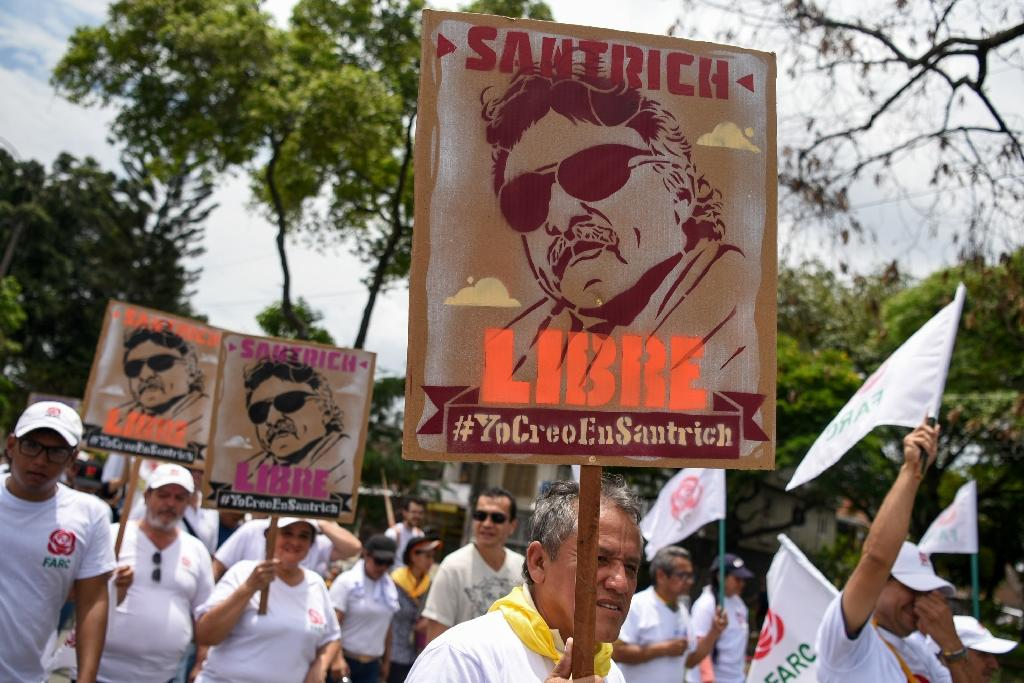 FARC supporters hold signs depicting former commander Santrich
