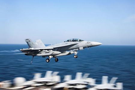 """An F/A-18F Super Hornet from the """"Patriots"""" of Electronic Attack Squadron (VAQ) 140 flies over the U. S. aircraft carrier USS Abraham Lincoln (CVN 72), in Arabian Sea,"""