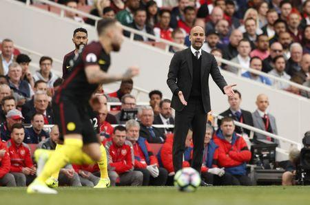 Técnico do Manchester City, Pep Guardiola assiste Nicolas Otamendi em ação.
