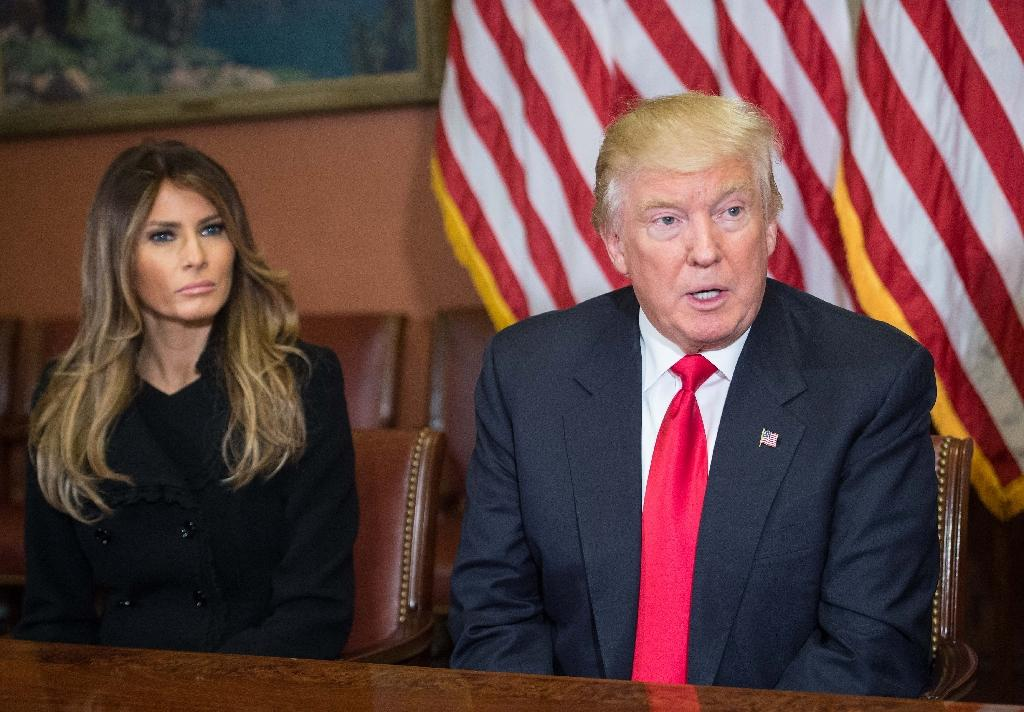 Melania Trump (L) listens to her husband US President-elect Donald Trump speak to the press at the US Capitol on November 10, 2016 (AFP Photo/Nicholas Kamm)