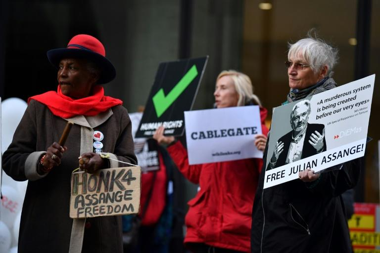 Protestors hold placards and shout slogans demanding the release of WikiLeaks founder Julian Assange, who faces extradition to the United States, as they gather outside the Old Bailey in the City of London on October 1, 2020