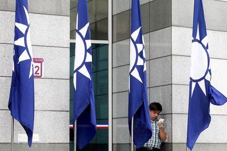 A man looks at his smartphone behind the Nationalist Kuomintang Party flags at its headquarters in Taipei, Taiwan, October 16, 2015. REUTERS/Pichi Chuang