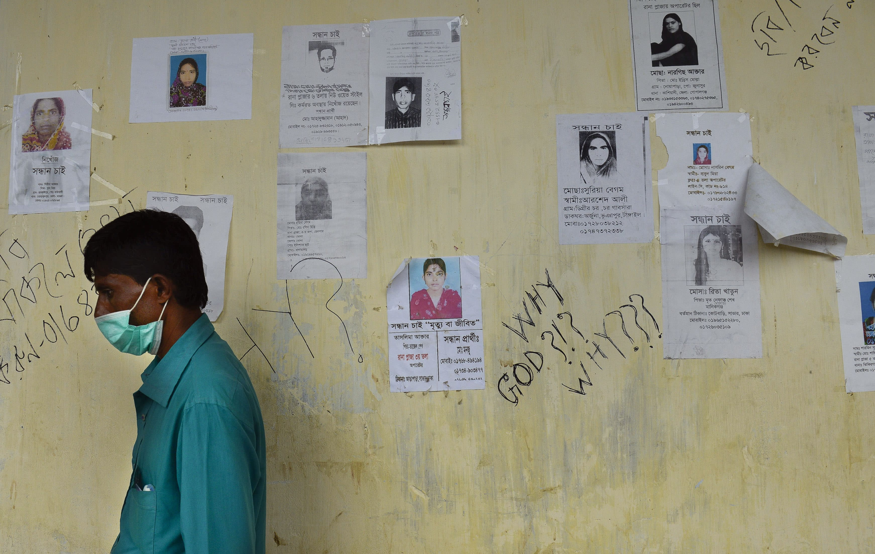 A Bangladeshi man walks past portraits of missing victims and graffiti written on the wall of a makeshift morgue in Savar, near Dhaka, Thursday, May 9, 2013. The death toll from the collapse of a garment factory building passed 900 on Thursday even as a fire in an 11-story garment factory Wednesday night in Dhaka killed eight people, including a ruling-party politician and a top official in the country's powerful clothing manufacturers' trade group. (AP Photo/Ismail Ferdous)