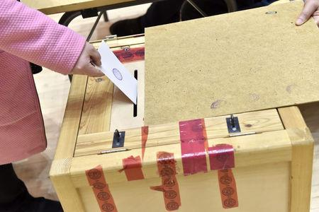 A voter casts her vote at Mantsala town hall during the Finnish parliamentary elections, in Mantsala