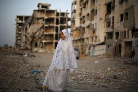 Palestinian girl stands near residential buildings that witnesses said were heavily damaged by Israeli shelling during a 50-day war last summer, in Beit Lahiya town in the northern Gaza Strip