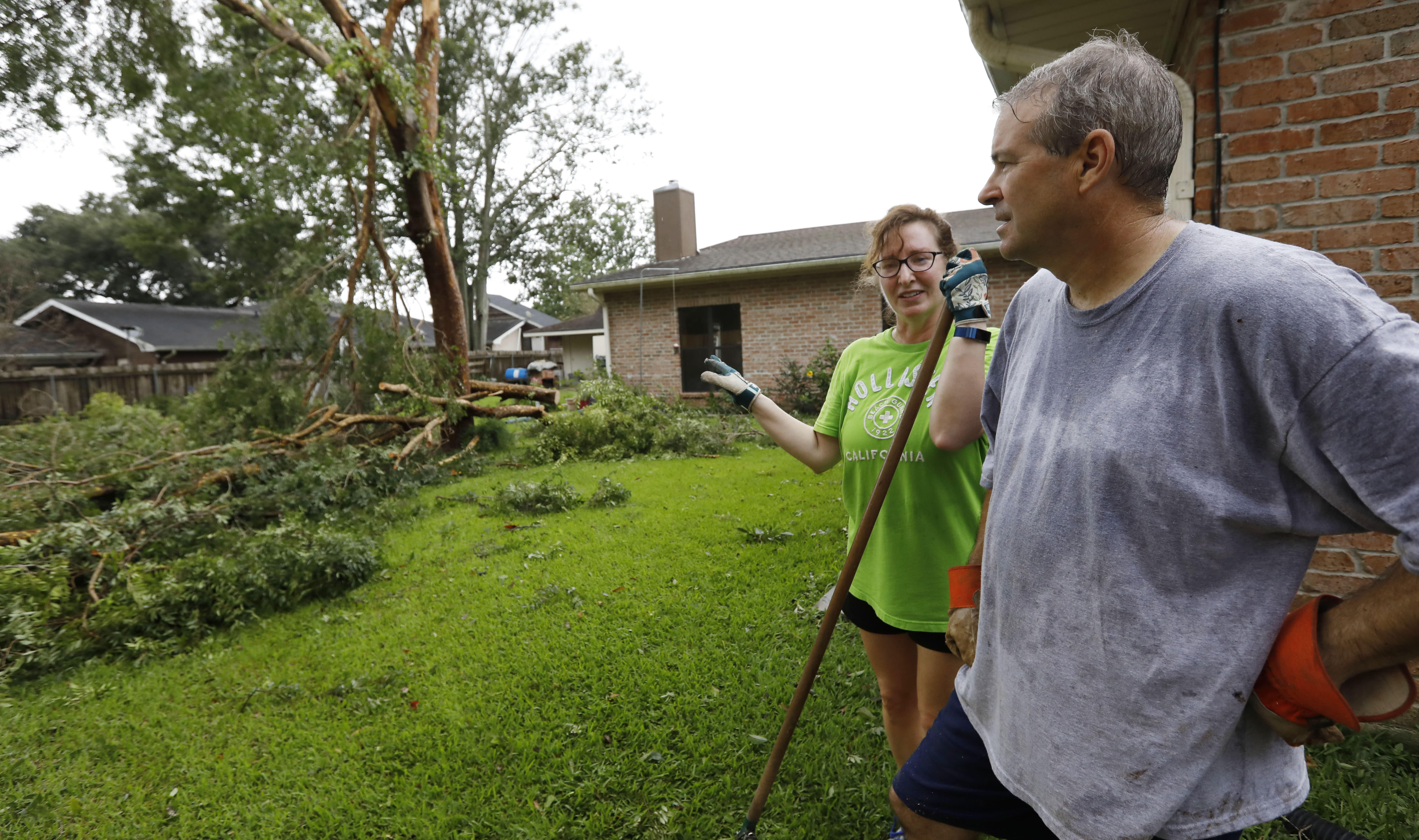 """""""At least it did not hit the house,"""" says Lois Bergeron, left, Sunday, July 14, 2019, as she and her husband Steve Bergeron take a break from cleanup after Tropical Storm Barry and look at their downwd backyard tree, in Morgan City, La. (AP Photo/Rogelio V. Solis)"""