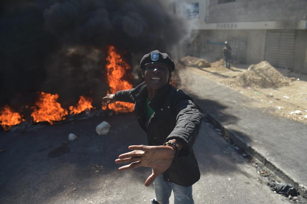 A demonstrator gestures in front of burning tires during protests in Port-au-Prince (AFP Photo/HECTOR RETAMAL)