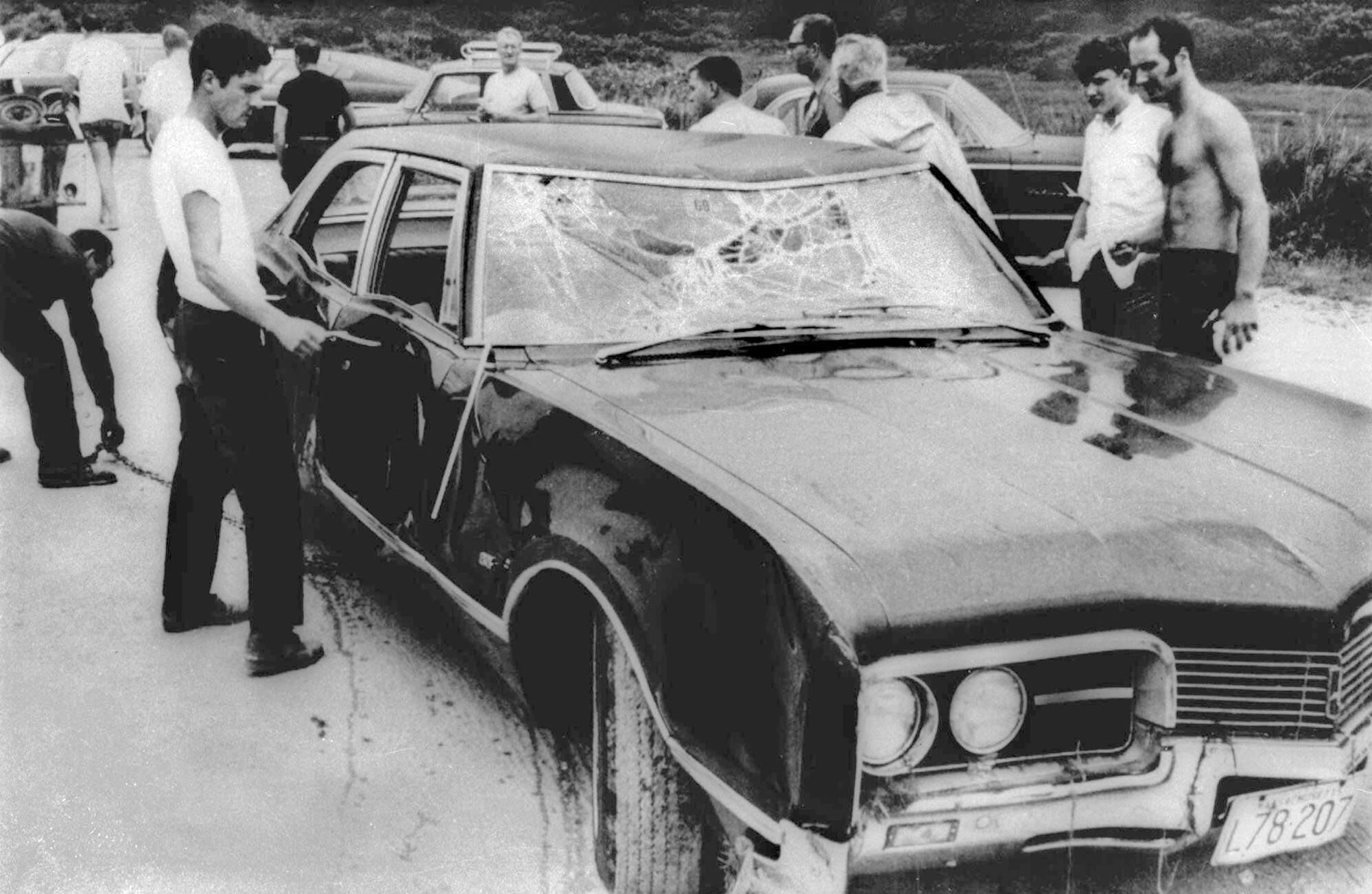 FILE - In this July 18, 1969 file photograph, curious onlookers inspect U.S. Sen. Edward Kennedy's car in Edgartown, Mass. Mary Jo Kopechne drowned after Kennedy drove the car off Dyke Bridge on Chappaquiddick Island, Mass. on July 18, 1969. It's been 50 years since the fateful automobile accident that killed a woman and thwarted Kennedy's presidential aspirations. (AP Photo, File)