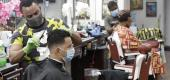 "Barbers Johnny ""Geo"" Sanchez, left, and Alberto Sagentin cut hair in Miami. (Wilfredo Lee/AP)"
