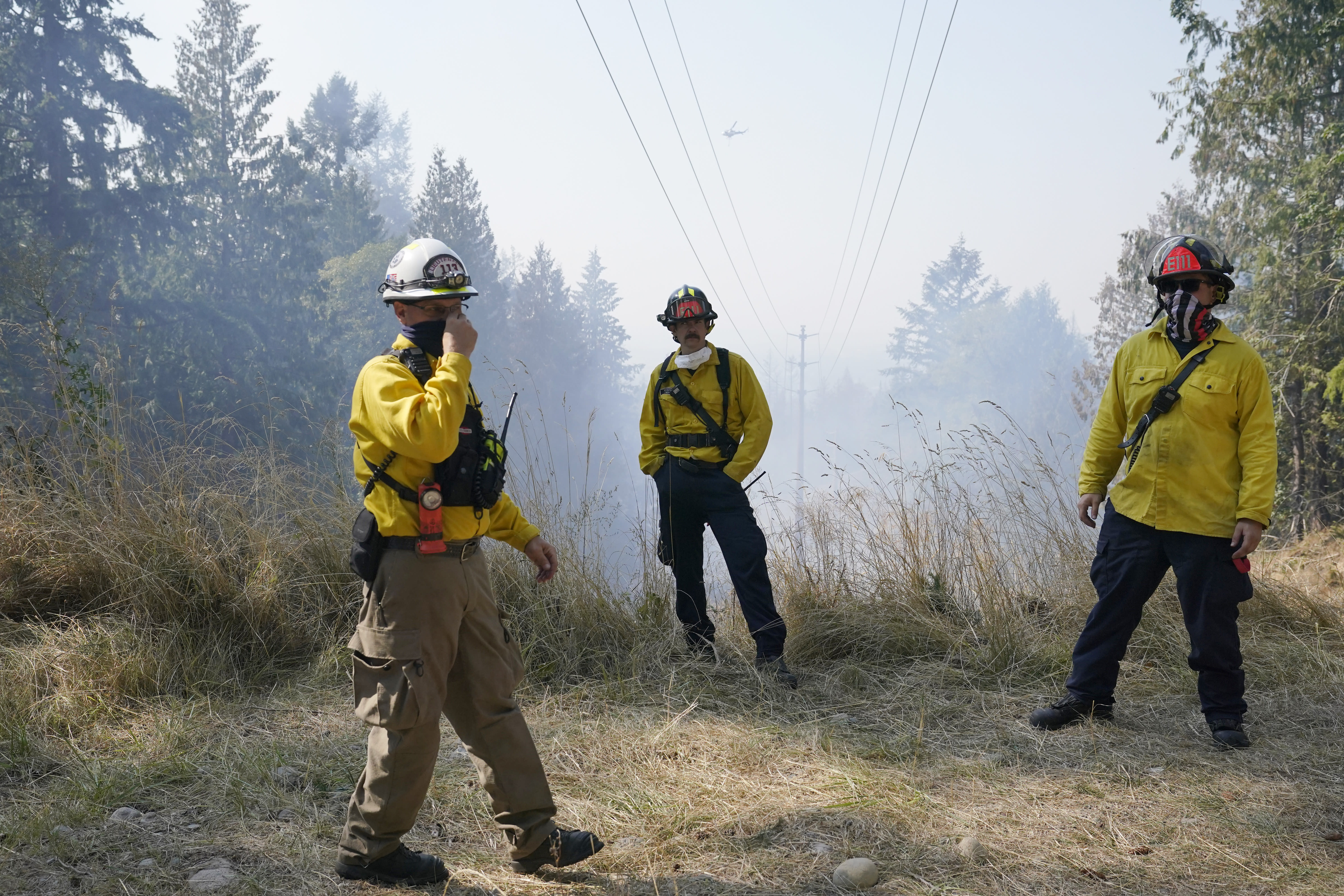 Firefighters wait under power lines for a helicopter to make a water drop, Wednesday, Sept. 9, 2020, on a hotspot of a wildfire burning in Bonney Lake, Wash., south of Seattle. (AP Photo/Ted S. Warren, Pool)