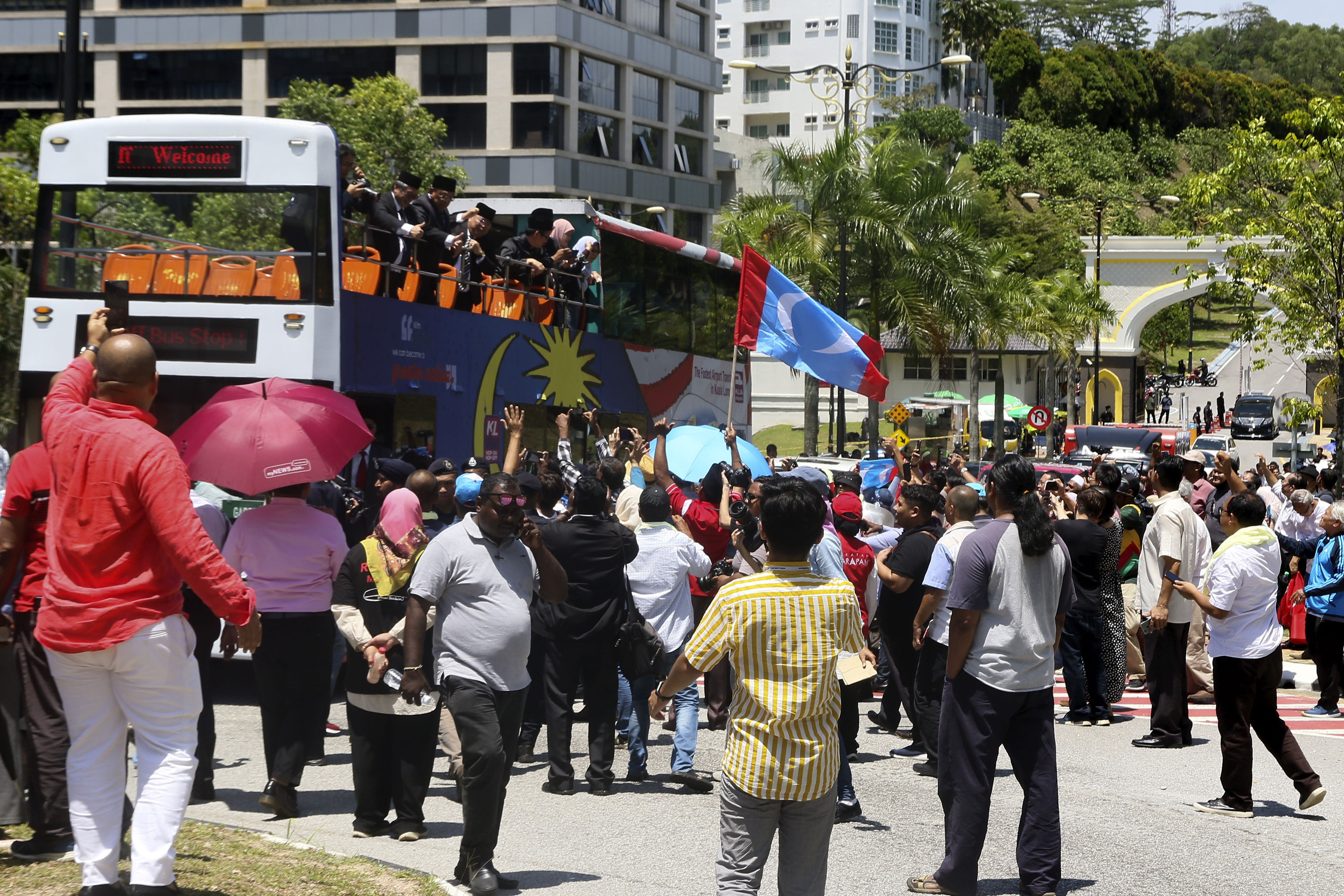 Lawmakers from the People's Justice Party on a double-decker bus wave to supporters as they head to the National Palace to meet the king in Kuala Lumpur, Malaysia, Wednesday, Feb. 26, 2020. Malaysia's king held unusual consultations with lawmakers for a second day Wednesday to resolve a political vacuum caused by the abrupt collapse of the ruling coalition and the resignation of Prime Minister Mahathir Mohamad. (AP Photo)