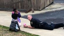 Mom records heartwarming video of police officer playing with dolls with girls who 'were afraid of cops'