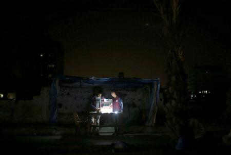 A Palestinian vendor uses battery-powered lights as he sells cigarettes during power cut at Shati refugee camp in Gaza City. REUTERS/Mohammed Salem