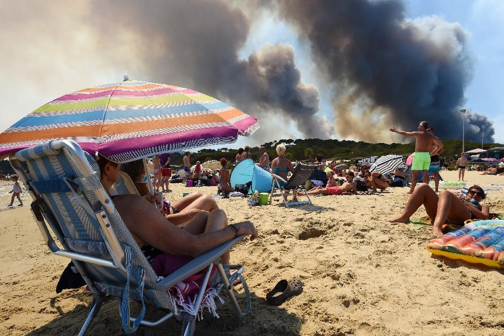 In the French village of Bormes-les-Mimosas, near beaches popular with tourists on the Cote d'Azur, fires that led to the evacuation of 10,000 people overnight Tuesday were largely extinguished (AFP Photo/Anne-Christine POUJOULAT )