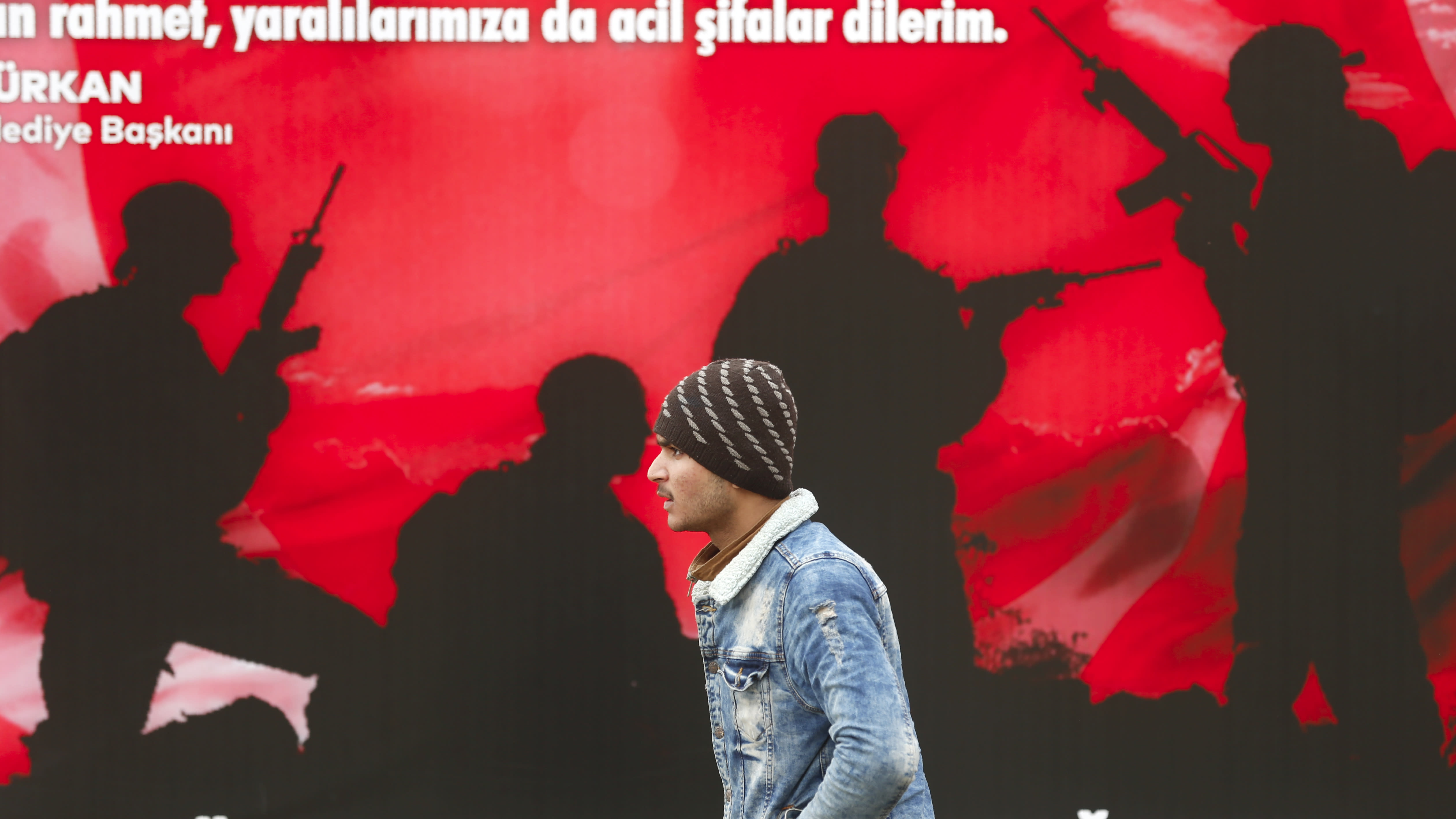 A migrant walks by a poster paying tribute to the fallen and wounded Turkish soldiers in Edirne near the Turkish-Greek border on Thursday, March 5, 2020. Turkey has vowed to seek justice for a migrant it says was killed on the border with Greece after Greek authorities fired tear gas and stun grenades to push back dozens of people attempting to cross over. Greece had denied that anyone was killed in the clashes. (AP Photo/Darko Bandic)