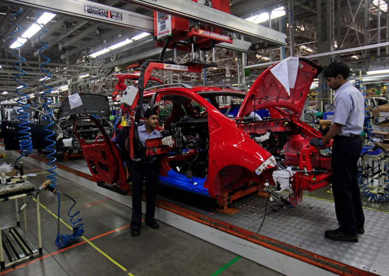 FILE PHOTO: Employees work on a Chevrolet Beat car on an assembly line at the General Motors plant in Talegaon