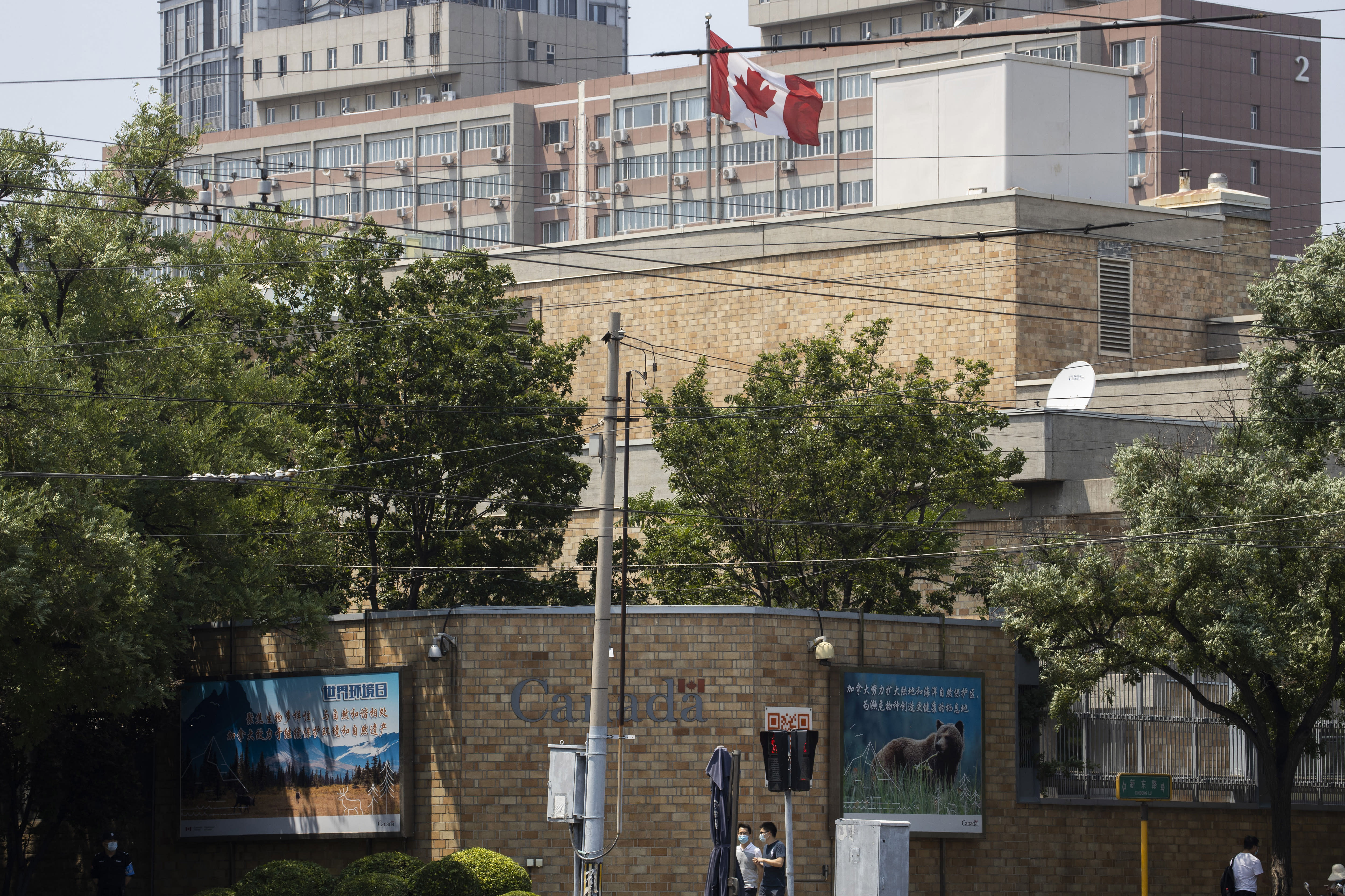 Residents pass by the Canadian Embassy in Beijing on Friday, June 19, 2020. Prosecutors charged two detained Canadians with spying Friday in an apparent bid to step up pressure on Canada to drop a U.S. extradition request for a Huawei executive under house arrest in Vancouver. (AP Photo/Ng Han Guan)