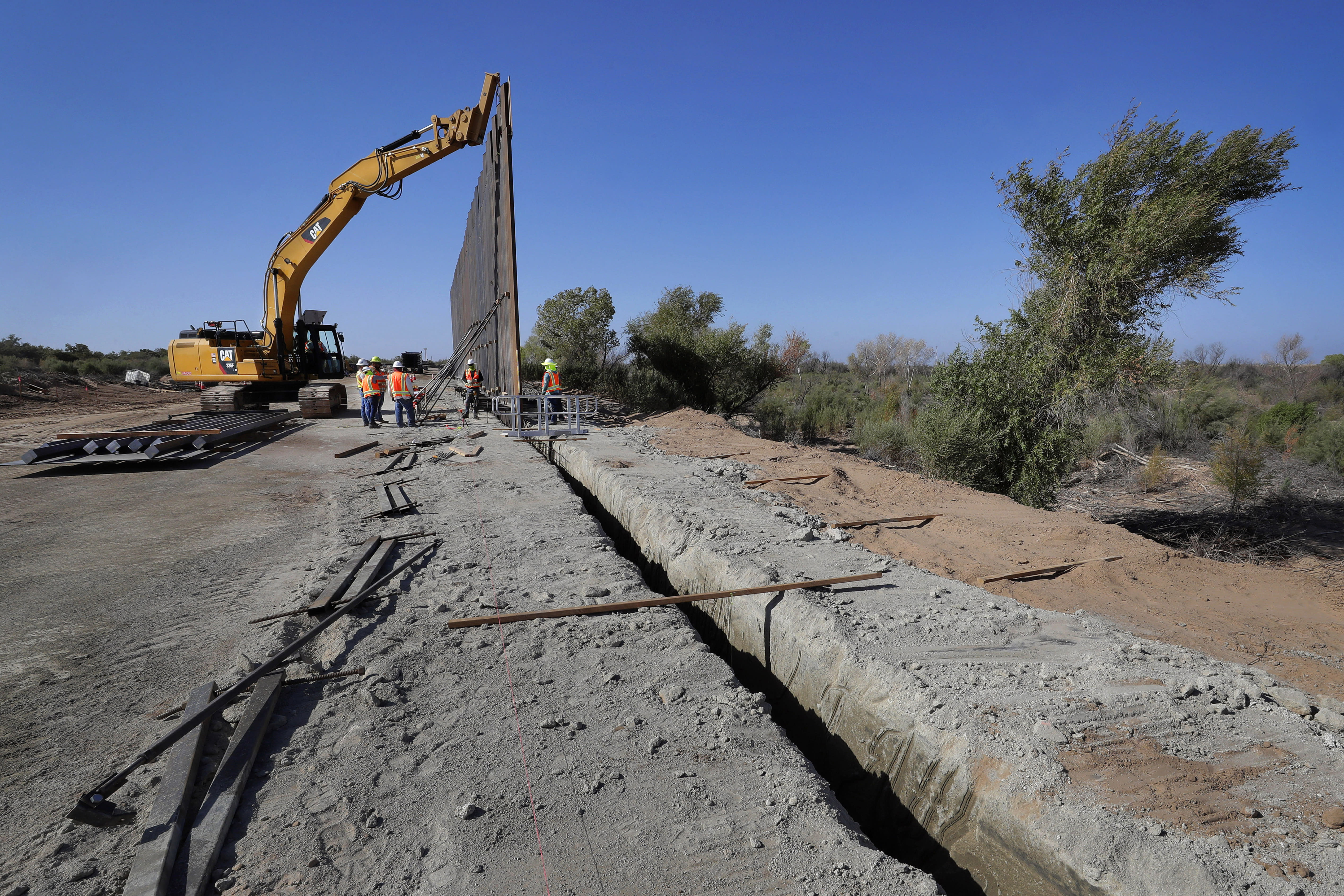 FILE - In this Sept. 10, 2019, file photo government contractors erect a section of Pentagon-funded border wall along the Colorado River, in Yuma, Ariz. The federal Bureau of Land Management said on Tuesday, July 21, 2020, it's transferred over 65 acres of public land in Arizona and New Mexico to the Army for construction of border wall infrastructure. (AP Photo/Matt York, File)