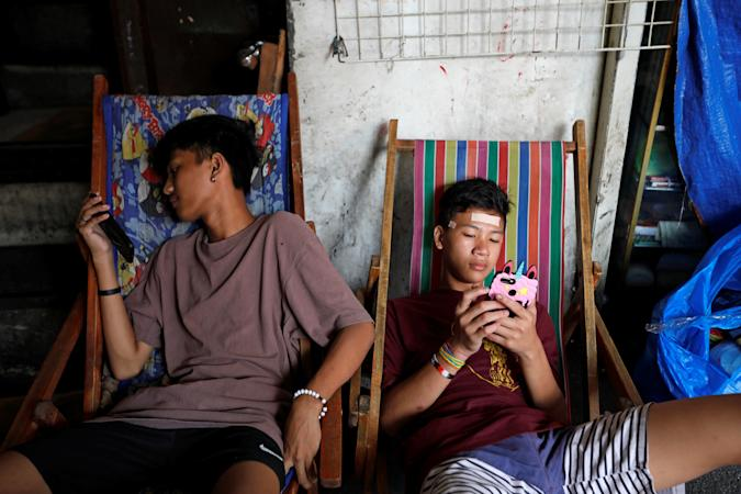 Youths use smartphones at Quiapo in Manila, Philippines, January 10, 2020. REUTERS/Willy Kurniawan