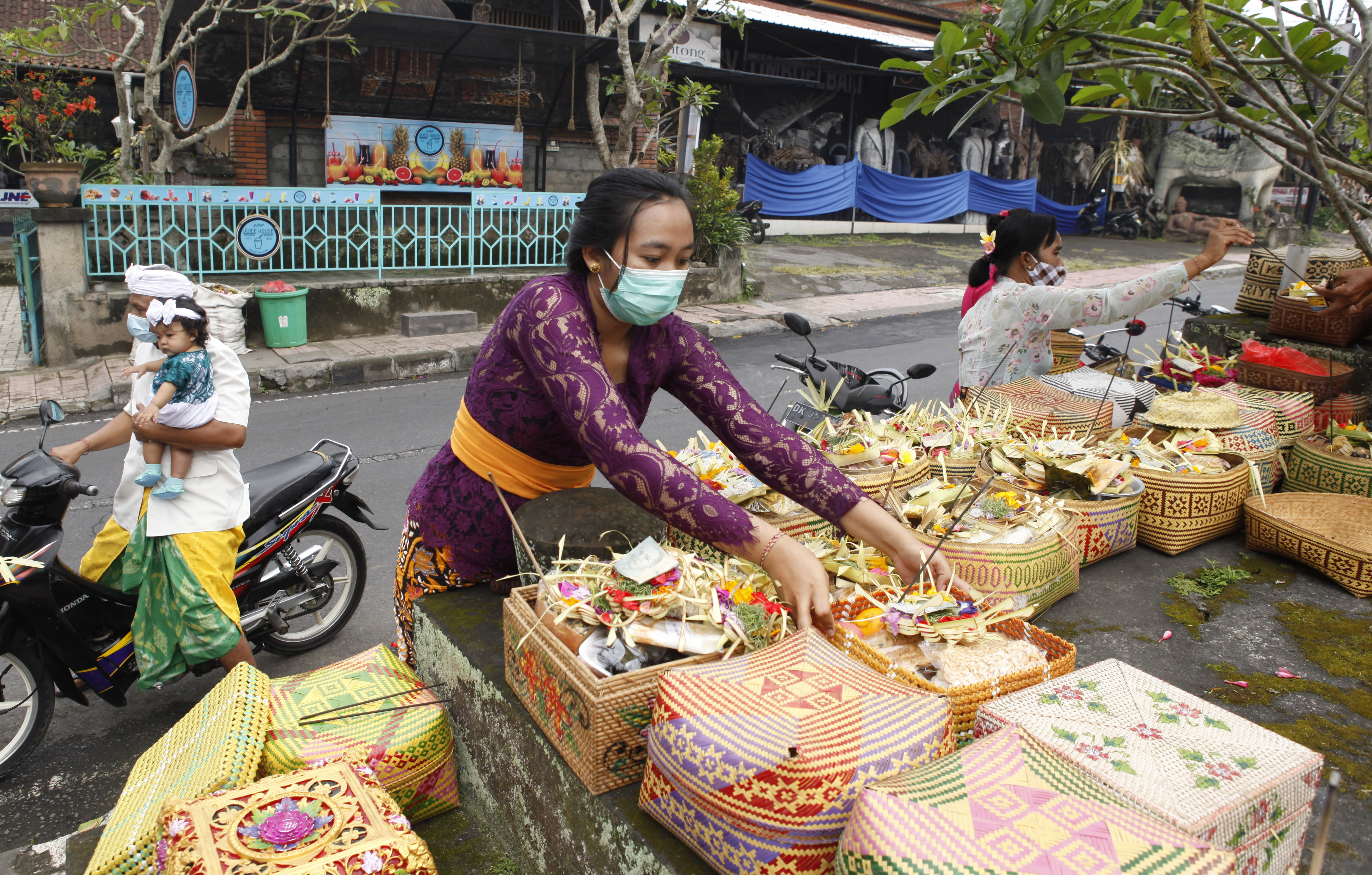 A woman gives an offering as she wears a face mask as a precaution against the new coronavirus outbreak during a Hindu ritual prayer at a temple in Bali, Indonesia, Wednesday, Sept. 16, 2020. (AP Photo/Firdia Lisnawati)