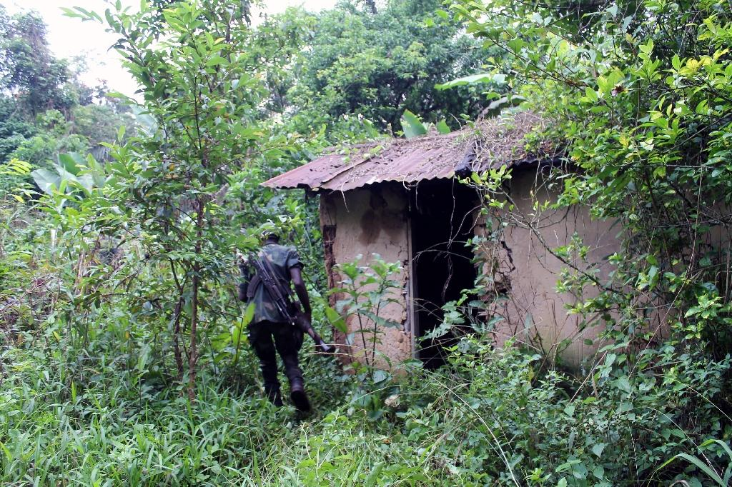A Democratic Republic of Congo soldier inspects on December 31, 2013 in Eringeti a house that shows remnants of troops from the Allied Democratic Forces and the National Army for the Liberation of Uganda (AFP Photo/Alain Wandimoyi)