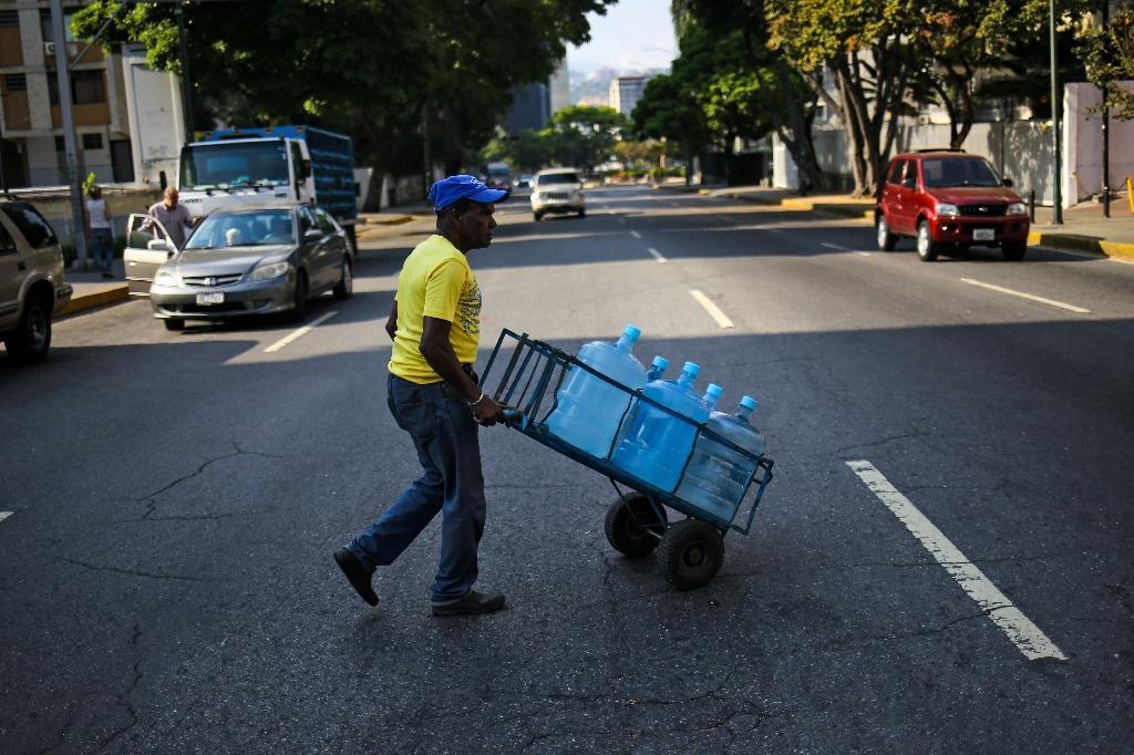 A man carries water cans in a wheelbarrow in Caracas (AFP Photo/Cristian HERNANDEZ)