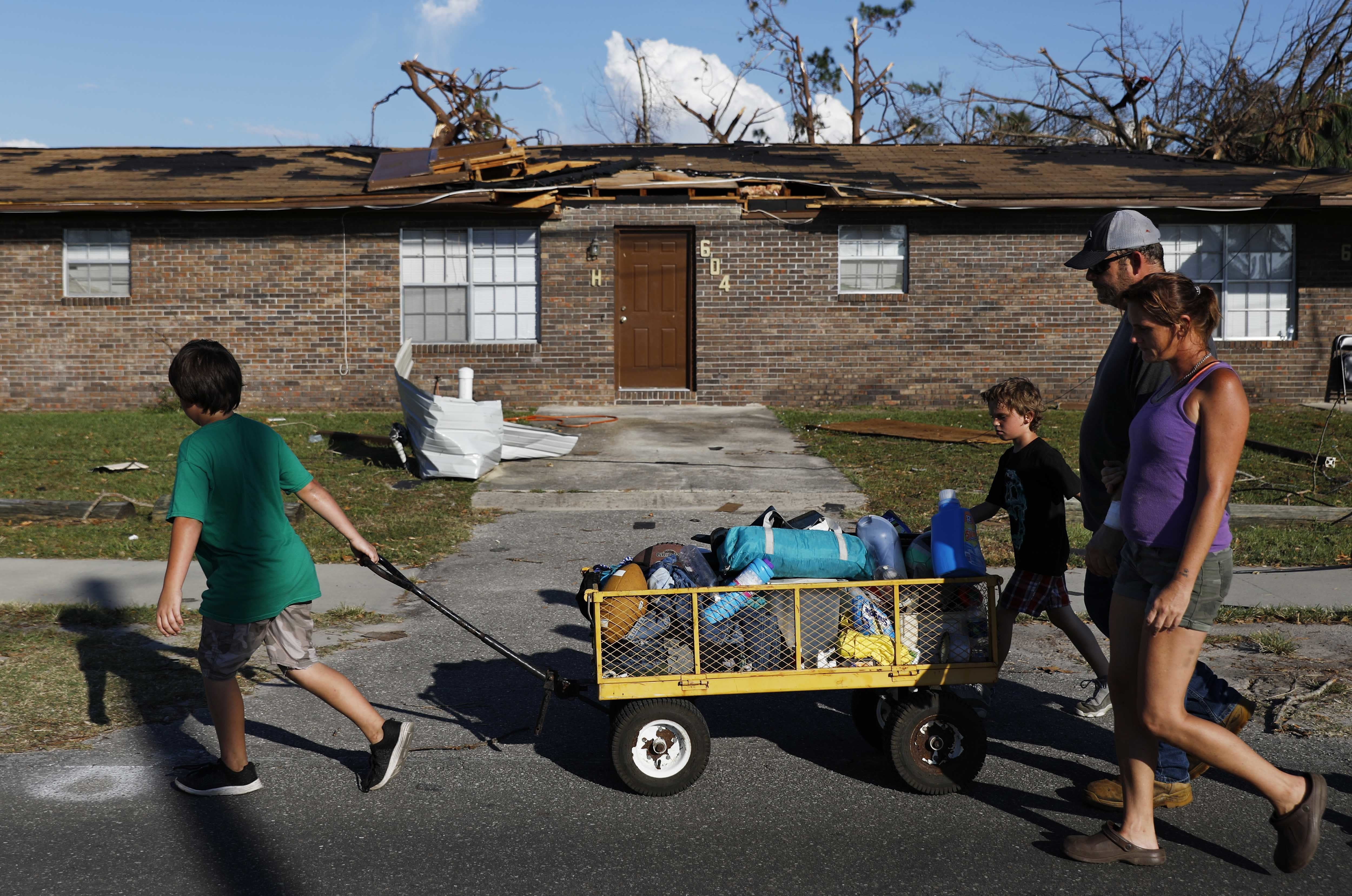 Anthony Weldon, 11, left, pulls a cart with his family's belongings as he relocates with his brother Thomas, 10, mother Dawn Clarke, right, and father Richard Coker from their uninhabitable damaged home to stay at their landlord's place in the aftermath of Hurricane Michael in Springfield, Fla., Monday, Oct. 15, 2018. (AP Photo/David Goldman)