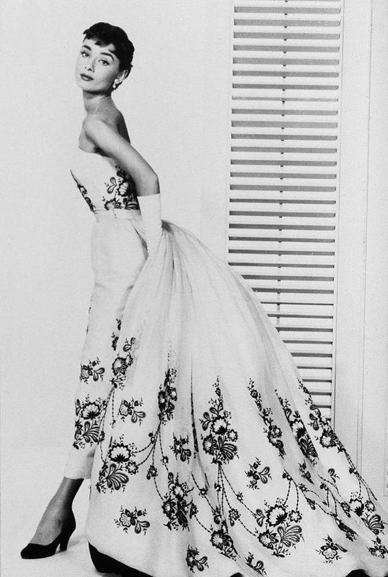 <p>For her film <em>Sabrina</em>, De la Renta created Hepburn's party gown featured on the movie poster. He would continue to dress her throughout her career, and the pair became close. In 1989, she escorted De la Renta to the CFDA Awards, wearing a feather-embellished creation by the designer.</p>