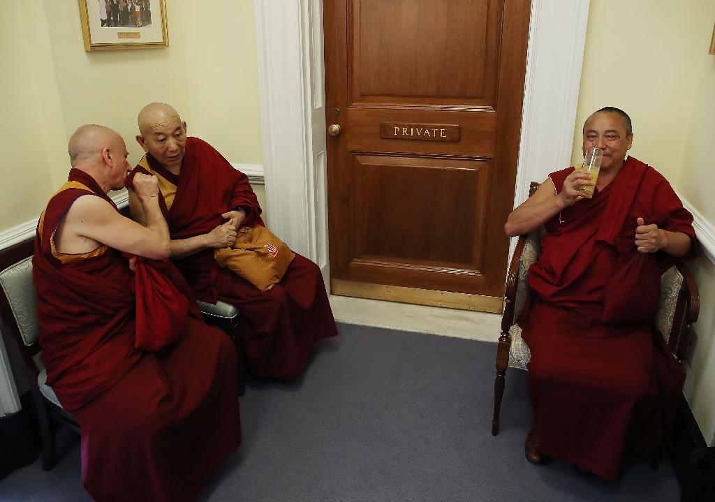 Buddhist Monks wait in the hallway while the Dalai Lama attends a meeting at the US Capitol on June 14, 2016 (AFP Photo/Mark Wilson)