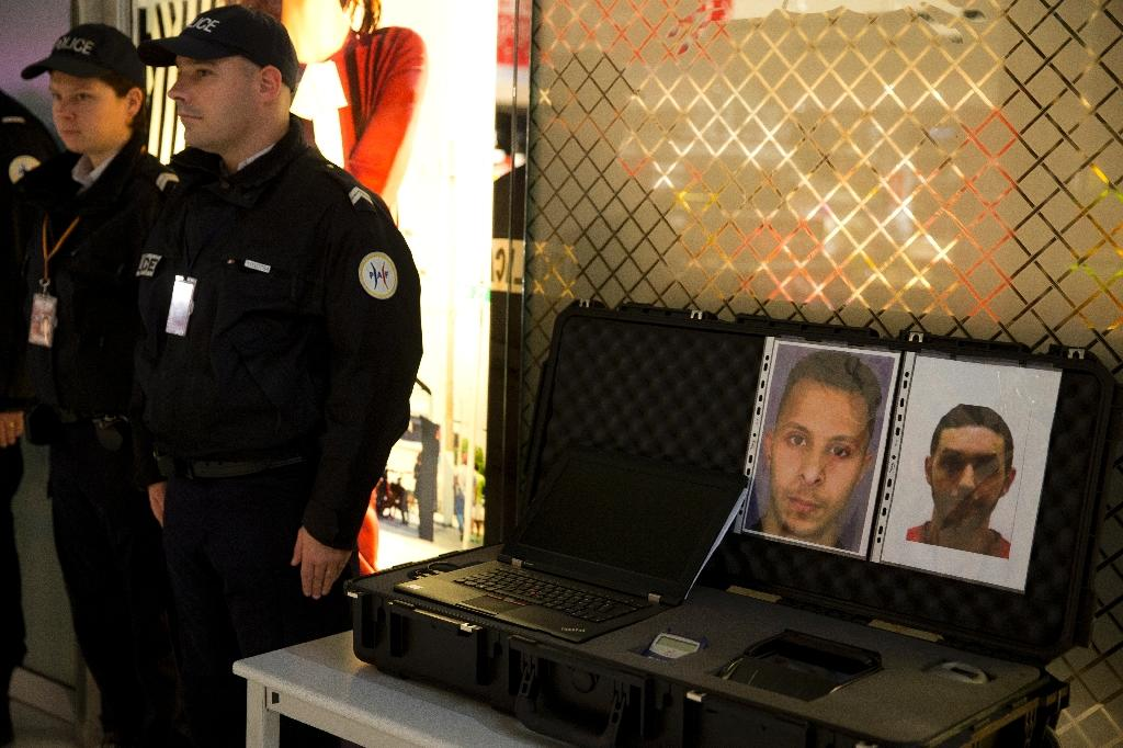 Police stand next to wanted posters for Salah Abdeslam (L) and Mohamed Abrini on December 3, 2015 at the Roissy-Charles-de-Gaulle airport, outside Paris (AFP Photo/Kenzo Tribouillard)