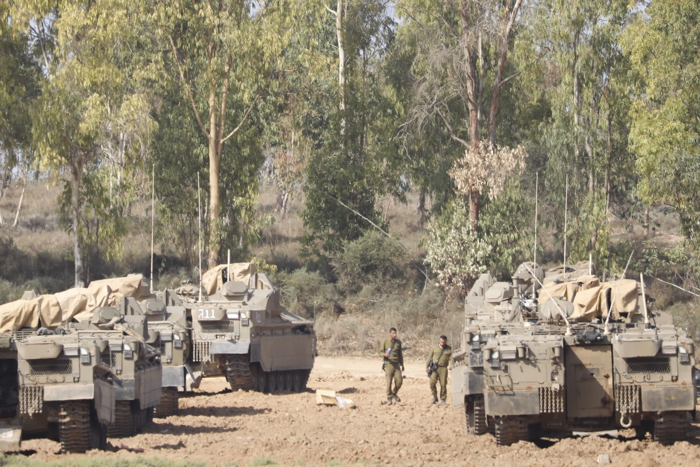 Israeli soldiers walk past military vehicles in a gathering point near the Israel-Gaza Border, Thursday, Nov. 14, 2019. Israel and the militant Islamic Jihad group in Gaza reached a cease-fire on Thursday to end the heaviest Gaza fighting in months. (AP Photo/Ariel Schalit)