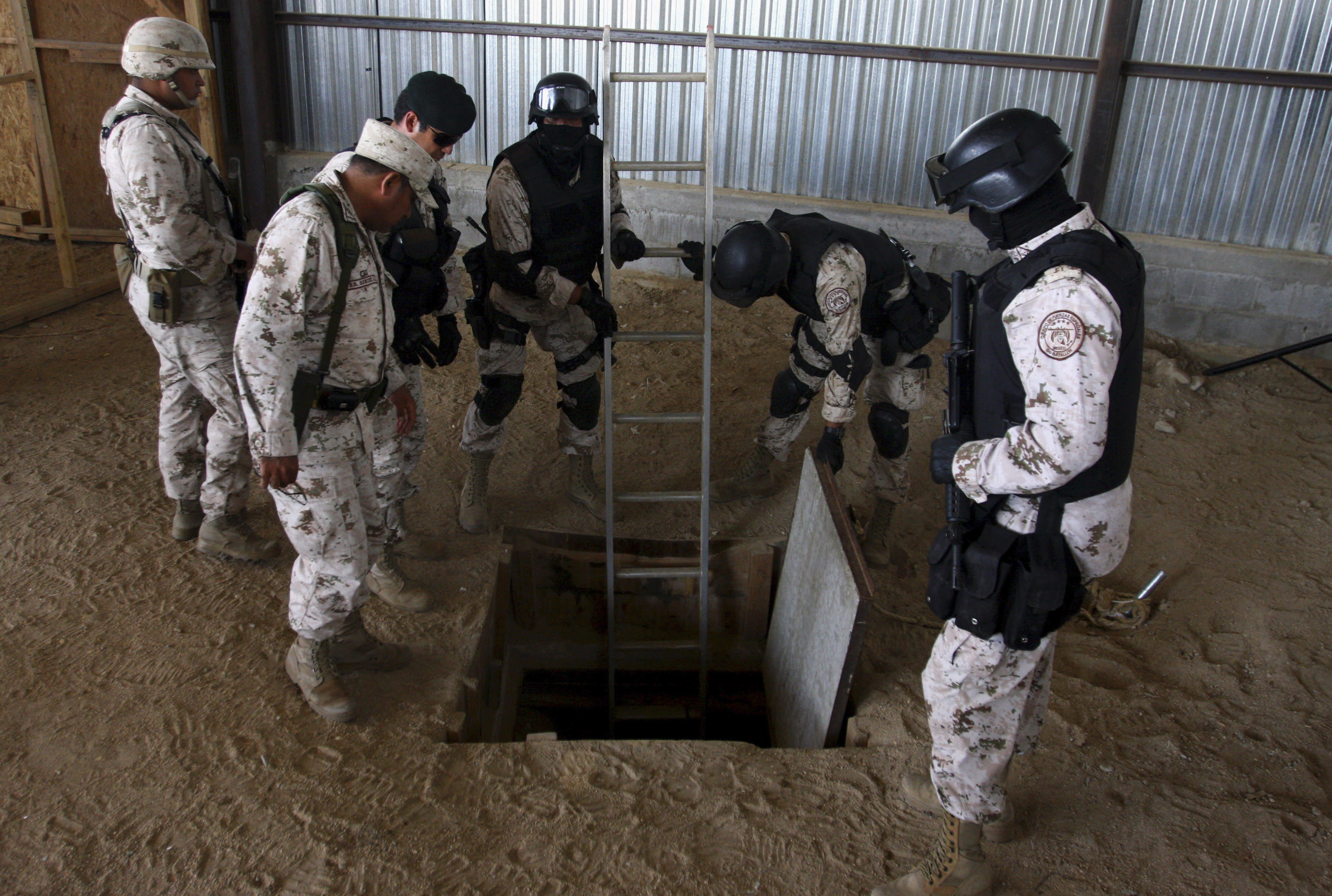 """Soldier prepare a ladder to enter a tunnel during a presentation to the media in Tijuana November 16, 2011. Police have discovered a """"major cross-border drug tunnel"""" running to California from Mexico, and seized 14 tons of marijuana, authorities said Wednesday. The tunnel links warehouses in an industrial park south of San Diego and the Mexican border city of Tijuana, the U.S. Immigration and Customs Enforcement agency said in a news release. REUTERS/Jorge Duenes (MEXICO - Tags: CRIME LAW DRUGS SOCIETY MILITARY)"""