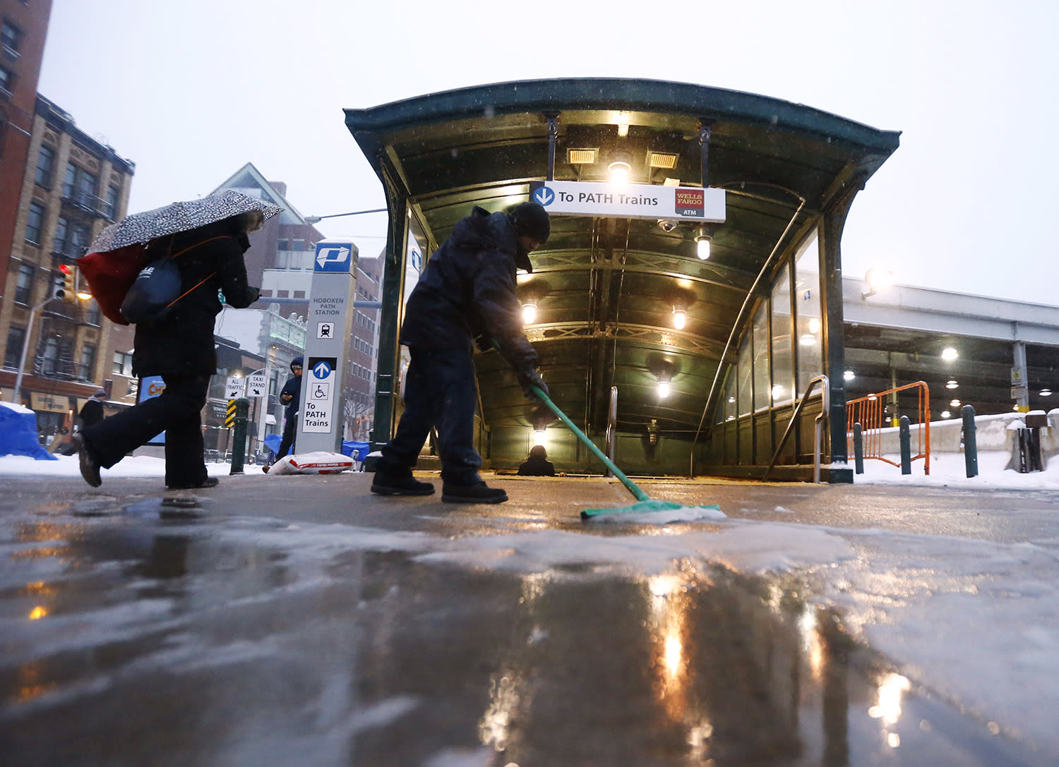 <p>A worker uses a squeegee to push snow and rain mixture away from the entrance of the Hoboken PATH train station during a snowstorm, Tuesday, March 14, 2017, in Hoboken, N.J. (Julio Cortez/AP) </p>