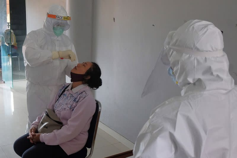 Healthcare worker takes a swab sample from a woman at a traditional market amid coronavirus disease (COVID-19) outbreak in Denpasar