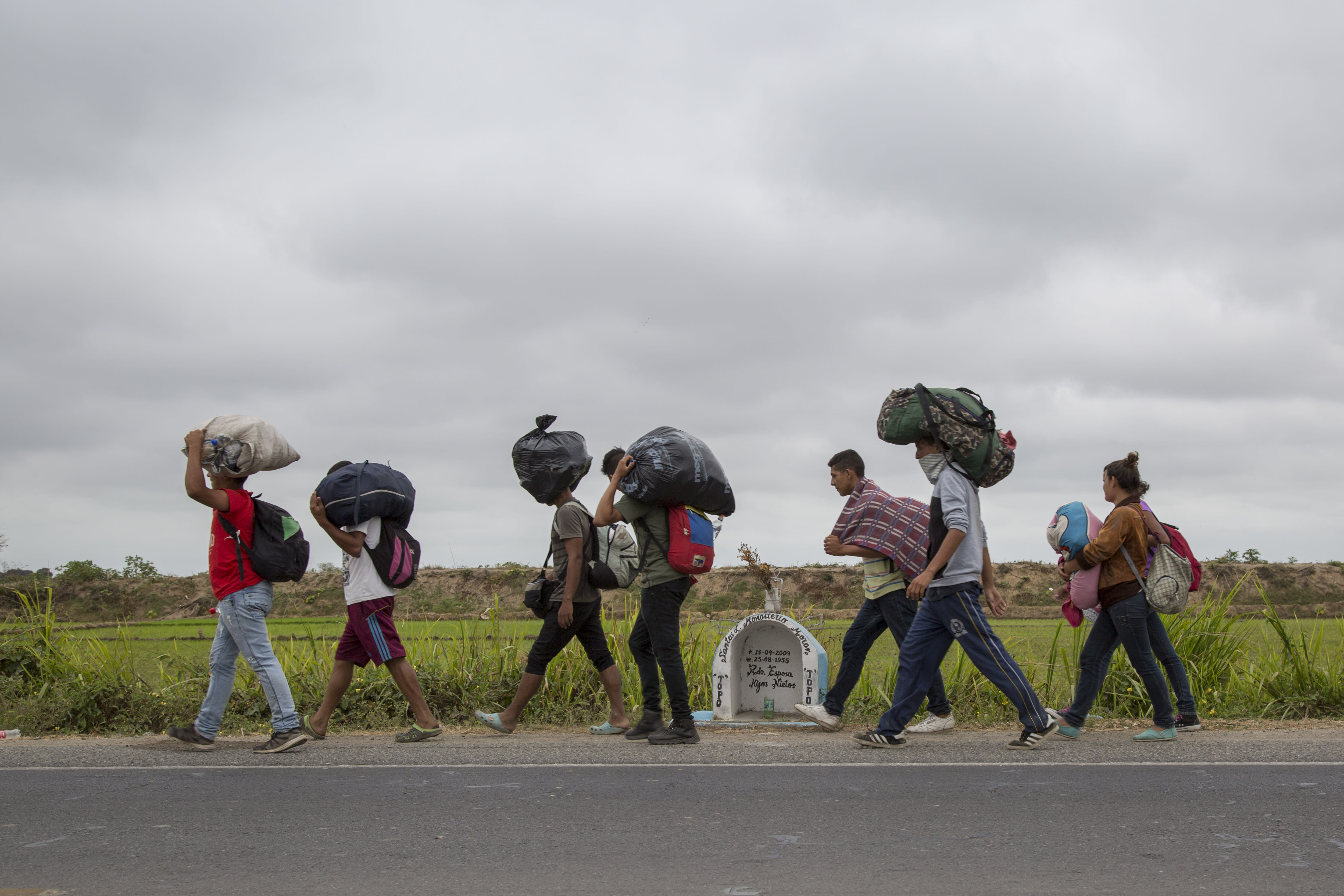 <p>A group of Venezuelans walk along the Panamericana route towards Lima on Aug. 14, 2018 in Tumbes, Peru. (Photo: Manuel Medir/Getty Images) </p>