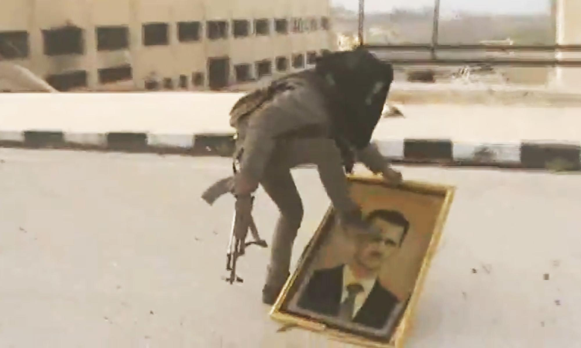 In this Sunday March 3, 2013 image taken from video obtained from the Shaam News Network, which has been authenticated based on its contents and other AP reporting, a Syrian rebel fighter stomps on a picture of Syrian President Bashar Assad within the police academy complex in Khan al-Asal, in the provence of Aleppo, Syria. The Britain-based Syrian Observatory for Human Rights said the rebels seized the police academy in Khan al-Asal after entering the sprawling government complex with captured tanks. The Observatory said the battle left at least 120 soldiers and 80 rebels dead. (AP Photo/Shaam News Network via AP video)
