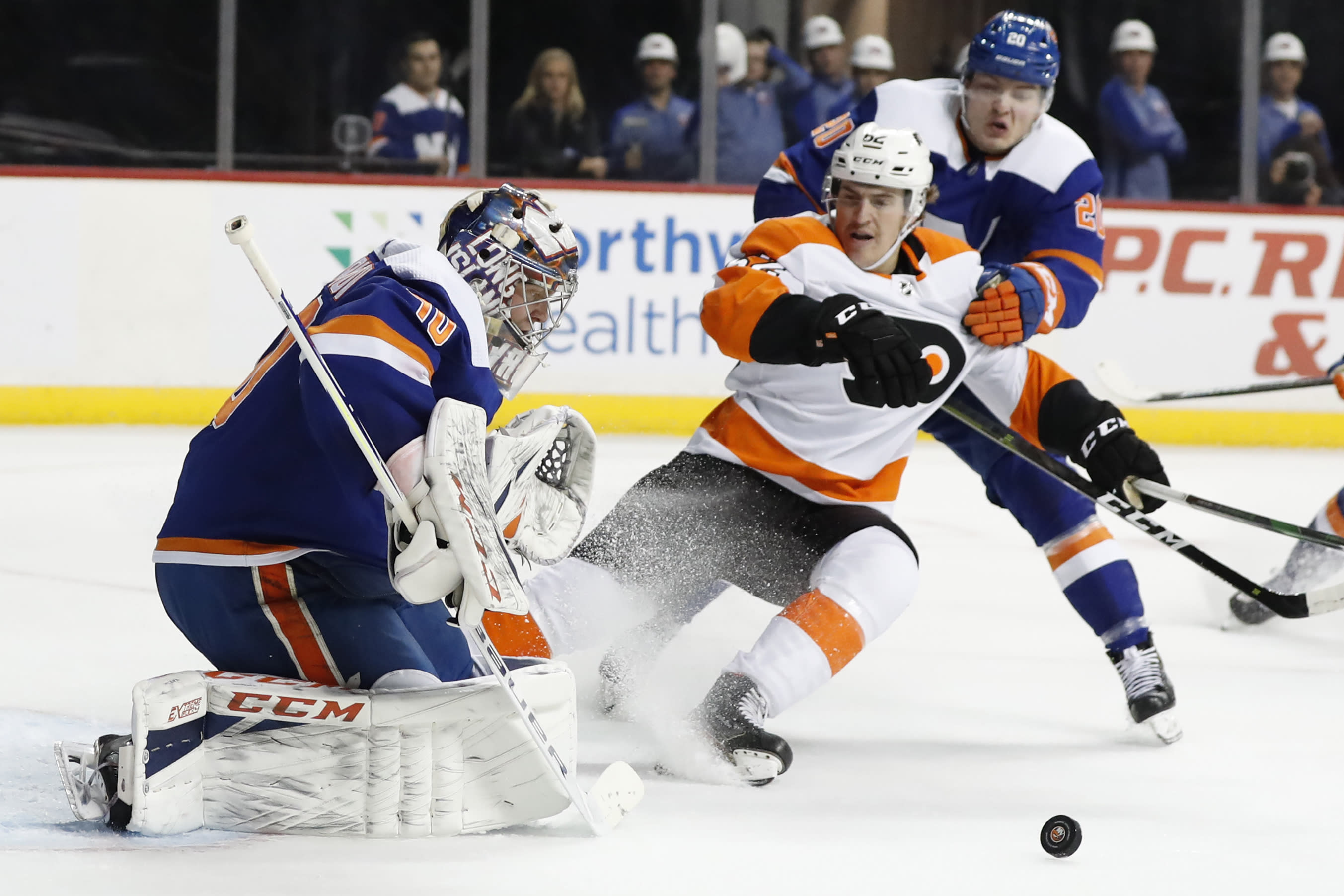 FILE - In This Feb. 11, 2020, file photo, New York Islanders goaltender Semyon Varlamov (40) deflects the puck as Islanders left wing Kieffer Bellows (20) keeps Philadelphia Flyers right wing Nicolas Aube-Kubel (62) away during the first period of an NHL hockey game in New York. The NHL ditched divisional playoffs to go back to the old-school format for its summer postseason and still ended up with all division rivals facing off in the second round. It's the Flyers against Islanders in the Metropolitan series. (AP Photo/Kathy Willens, File)