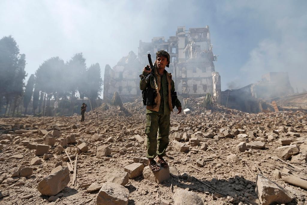 Yemeni Huthi rebel fighters inspect the damage after a reported Saudi-led coalition air strike hit presidential palace in the capital Sanaa on December 5, 2017 (AFP Photo/)