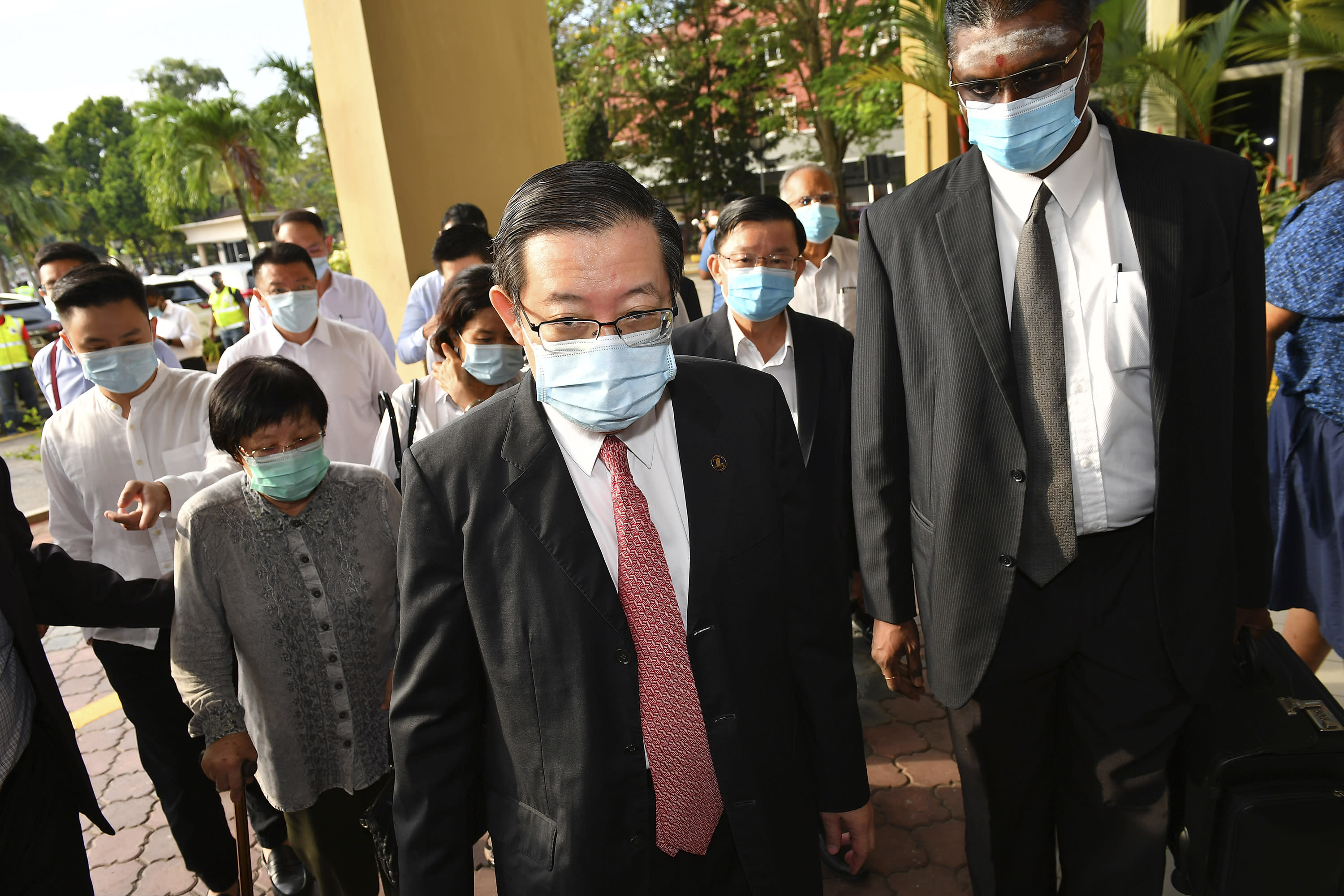 Malaysian former Finance Minister and Penang Chief Minister Lim Guan Eng, center, arrives at courthouse in Butterworth, Malaysia, Monday, Aug. 10, 2020. Lim pleaded not guilty to a second graft charge relating to a $1.5 billion undersea tunnel project. Lim has slammed the charges as political persecution by the new government. (AP Photo/Gary Chuah)