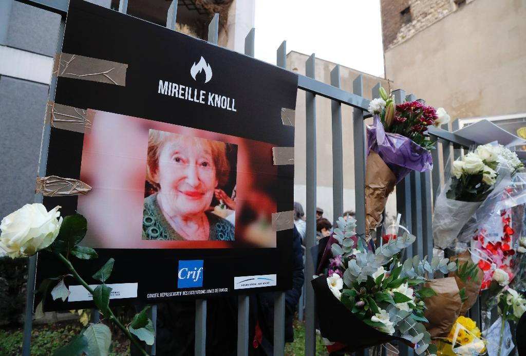 A photograph of Mireille Knoll and flowers are placed on the fence surrounding her building in Paris on March 28, 2018, in memory of the 85-year-old Jewish woman murdered in her home in what police believe was an anti-Semitic attack (AFP Photo/FRANCOIS GUILLOT)
