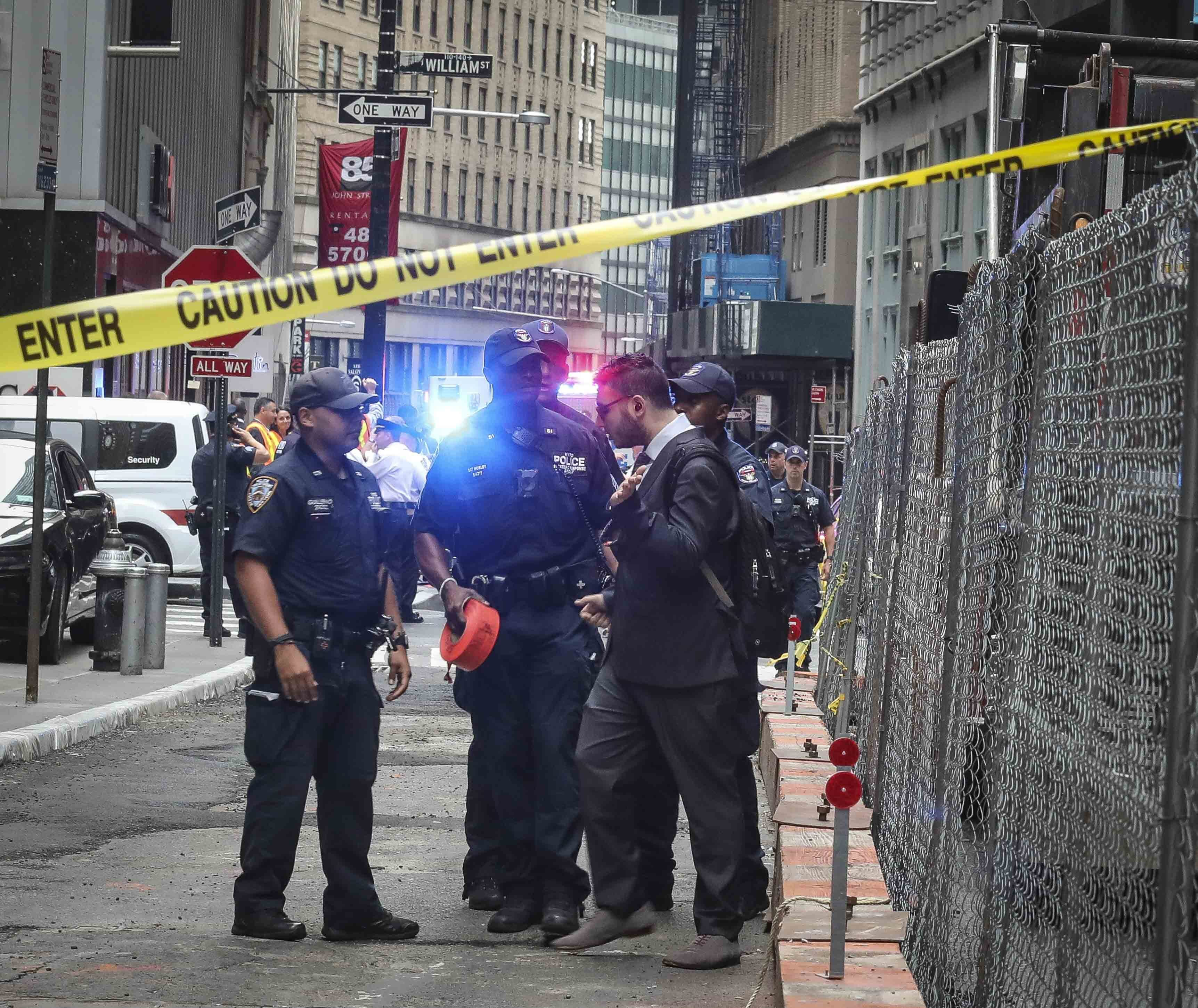NYPD officers block an individual attempting to bypass a taped-off zone, as police seal off area in the financial district around the the Fulton Street subway hub to investigate a suspicious item, Friday Aug. 16, 2019, in New York. Two abandoned objects that appeared to be pressure cookers prompted an evacuation of a major lower Manhattan subway station during the morning commute Friday before police determined they were not explosives, and authorities were investigating whether they were deliberately positioned to spark fear. (AP Photo/Bebeto Matthews)