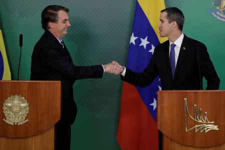 Venezuelan opposition leader Juan Guaido shakes hands with Brazil's President Jair Bolsonaro after a meeting in Brasilia, Brazil February 28, 2019. REUTERS/Ueslei Marcelino