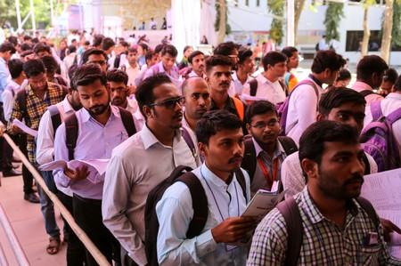 FILE PHOTO: Job seekers line up for interviews at a job fair in Chinchwad