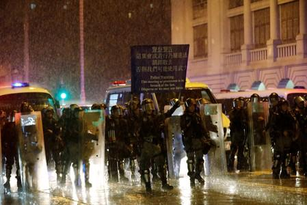 Riot police officers raise a warning flag as they stand guard during a protest in Hong Kong